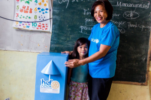 Teacher and student standing by a water filter supplied by Rotary