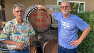 Photo of two men standing in front of a wine keg.